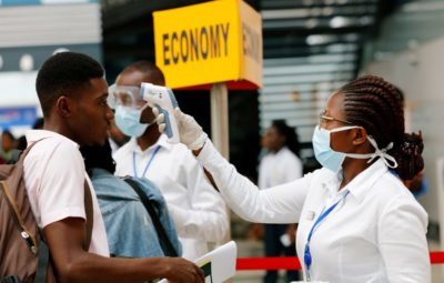 A health worker checks the temperature of a traveller as part of the coronavirus screening procedure at the Kotoka International Airport in Accra, Ghana